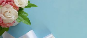 Bouquet of roses, silk ribbon on blue background. royalty free stock photos