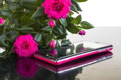 Bouquet of roses and a smartphone. Smartphone  and bouquet of roses on a black background Stock Photo