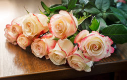Bouquet of roses on the table. On the table lies a beautiful bouquet of white roses stock photo