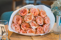 Bouquet of roses on the table. Bouquet of pink David Austin Roses roses packed in white craft on the wooden table Stock Photo