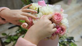 Making flower composition in pink and white colors. Bouquet with roses, tulips, hydrangea and greens in floral store. Making flower composition in pink and white stock video