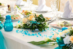 Bouquet of roses and turquoise decoration on the wedding table Stock Photos