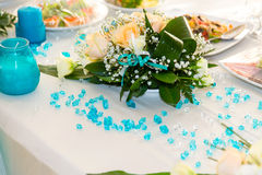 Bouquet of roses and turquoise decoration on the wedding table Royalty Free Stock Photo