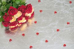 Bouquet of roses of two colors for beloved, many red hearts, silver background, symbol of love,Valentine`s feast and Royalty Free Stock Image