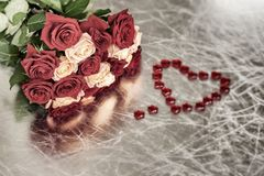 Bouquet of roses of two colors for beloved and red heart, symbol of love, Valentine`s feast, other romantic celebrations Royalty Free Stock Photo