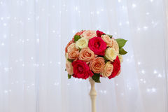 Bouquet of roses in a vase on the background of a silk curtain Stock Photos