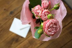 A bouquet of roses in a vase with envelope on wooden background royalty free stock image