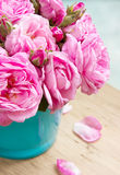 Bouquet of roses in vase on wooden table closeup. Royalty Free Stock Photo
