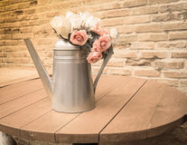 Bouquet of roses in watering can vase on table, vintage style Stock Photos