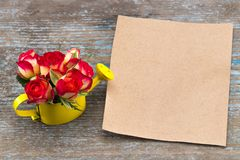 Bouquet of roses in watering can, vintage sheet of paper, and pe royalty free stock photography