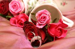 Bouquet of roses with wedding rings. Small bouquet of red and pink roses in a vase with two wedding rings. Very shallow depth of field, macro shot Royalty Free Stock Photography