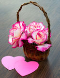 Bouquet of roses is in a wicker basket. And two hearts Stock Image