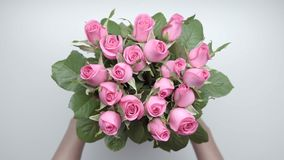 Bouquet of roses. 3. Women`s hands pick up a bouquet of pink roses from the table. 3 stock video footage