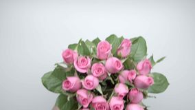 Bouquet of roses. 1. Women`s hands put a bouquet of pink roses on the table. 1 stock video footage