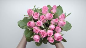 Bouquet of roses. 2. Women`s hands put a bouquet of pink roses on the table. Slow motion. 2 stock footage