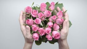 Bouquet of roses. Women`s hands touch a bouquet of pink roses on the table. Slow motion stock footage
