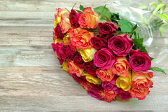 A bouquet of roses on a wooden background close up Royalty Free Stock Photo