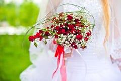 Bouquet rouge dans des mains de la jeune mariée Photographie stock