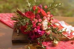 Bouquet rouge de mariage avec le décor de mariage sur une table Image libre de droits