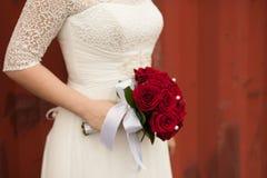 Bouquet rouge de mariage dans des mains de la jeune mariée contre une barrière rouge Images stock