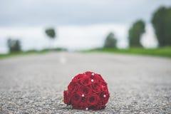Bouquet rouge de mariage sur le trottoir avec une bande de division blanche Photographie stock libre de droits