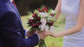 Bouquet rouge et blanc nuptiale dans des mains des nouveaux mariés banque de vidéos