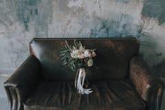 Bouquet rustique de mariage avec les roses légères et d'autres fleurs sur un sofa brun de luxe Photos stock