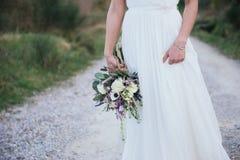 Bouquet rustique de mariage dans la main de sa jeune mariée, dehors Images libres de droits