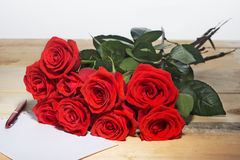 Bouquet of scarlet roses on a surface from wooden boards and the sheet  paper for writing  the text Royalty Free Stock Image