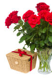 Bouquet of scarlet roses in vase with gift basket Stock Photos