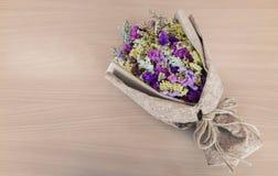Bouquet sec de vintage enveloppé en vieux papier sur le fond en bois image libre de droits