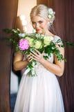 Bouquet sentant de belle jeune mariée des fleurs Photos stock