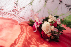 Bouquet in the shade of umbrella. Bouquet in the shade of lace umbrella Stock Photo
