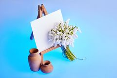Bouquet of snowdrops and a small easel with a white paper and mini jars on a blue background stock photos