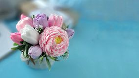 Bouquet of soap flowers on blurred blue background. stock photography