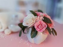 Bouquet of soap roses in vase, towel, cosmetic products on pink background. royalty free stock photo