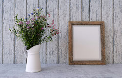 Bouquet of spring field flowers with frame. Bouquet of spring field flowers in a vase on a white vintage wooden board home decor in a rustic style with frame Royalty Free Stock Images