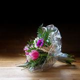 Bouquet of  spring flowers in cellophane on wood, dark backgroun Royalty Free Stock Image