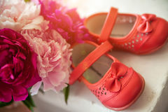 Bouquet of spring flowers and children's shoes Royalty Free Stock Photo