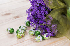 Bouquet of spring flowers with chocolate eggs Stock Photos