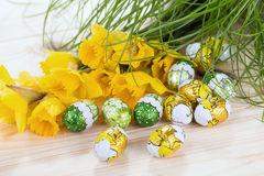 Bouquet of spring flowers with chocolate eggs Stock Photo