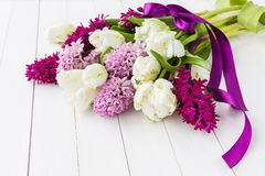 Bouquet of spring flowers decorated with purple ribbon on white wooden table Stock Photography