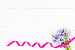 Bouquet of spring flowers decorated with ribbon on white wooden background. Top view, copy space Stock Photography