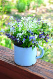 Bouquet of spring flowers in an iron cup.  Royalty Free Stock Photo