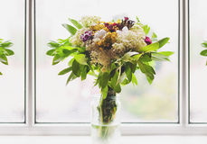 Bouquet of spring flowers at the window Stock Photo
