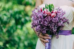Bouquet of spring lilac flowers in young girls hands on green background. Close up picture stock photo