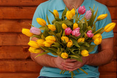 Bouquet of spring tulips in the hands of men on wooden background. Bouquet of spring yellow tulips in the hands of man on wooden background Royalty Free Stock Images