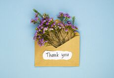 A bouquet of spring wildflowers in an envelope and the inscription thank you