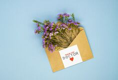 A bouquet of spring wildflowers in an envelope and the inscription thank you to the doctor