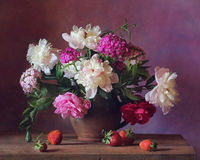 Bouquet. Still life with strawberries and a bouquet of roses and peonies Stock Photography